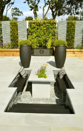 Low maintenance garden with a stone patio and sunken seating area