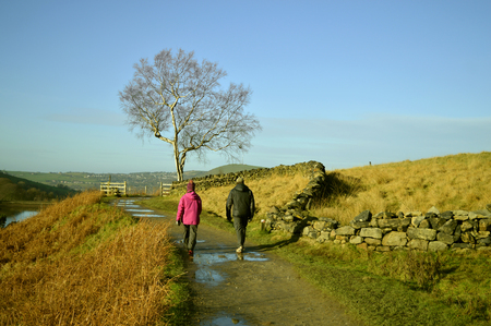 A couple walking in the Peak District National Park above Dovestone reservoir in Greenfield, on Saddleworth Moor in Greater Manchester