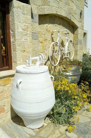 Weiß lackiertes Fahrrad und eine Nähmaschine auf einer Urne, die in einem Garten auf Kreta, einer der griechischen Inseln, bemalt wurde?