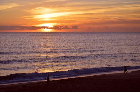 Tourists walking along Praia Da Gale Beach at sunset on the Algarve coast