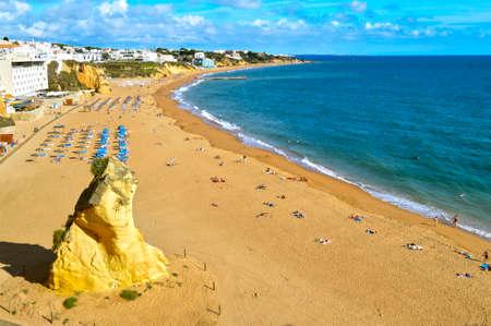 Tourists enjoying the sun on Albufeira Beach in Portugal