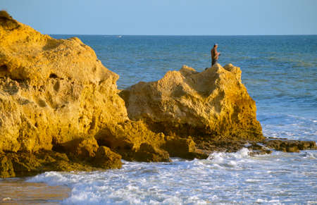 Man fishing form the rock formations on Sietskes Beach on the Algarve coast