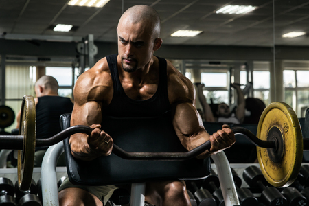 White Muscular man training his arms in the gym by dumbell in the curl bench Stock Photo