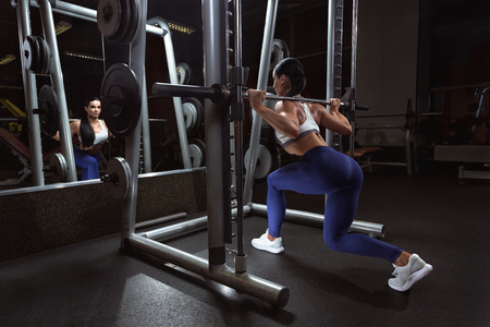 Pretty young woman is doing squats with barbell in the training apararus in gym
