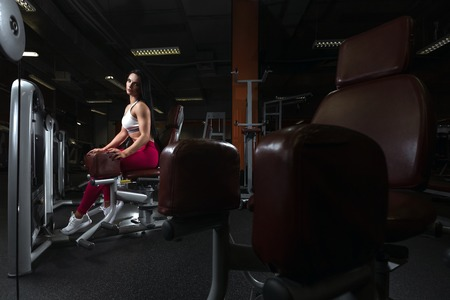 Pretty young brunette girl is relaxing in legs training apparatus in the gym