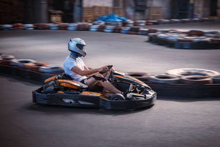 Male driving a kart on an indoor track
