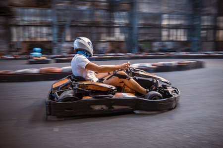Male driving a kart through a turn on an indoor track
