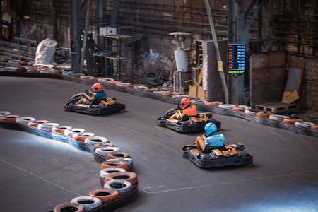 Three guys racing with go karts indoors