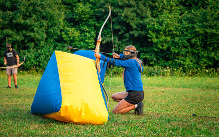 Girl kneeling behind an inflatable protection in order to get a good position to shoot her arrow