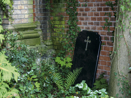 mortician: A blank marble headstone leaning on the cemetery wall  Stock Photo