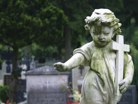 Stenen beeld van een kind met een kruis