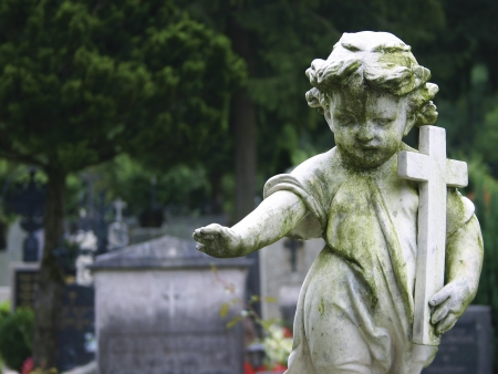 Stone statue of a child holding a cross