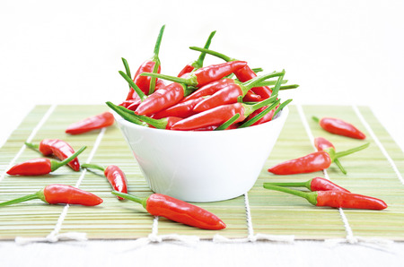tabasco: Red hot chili peppers in a white bowl on a green bamboo mat