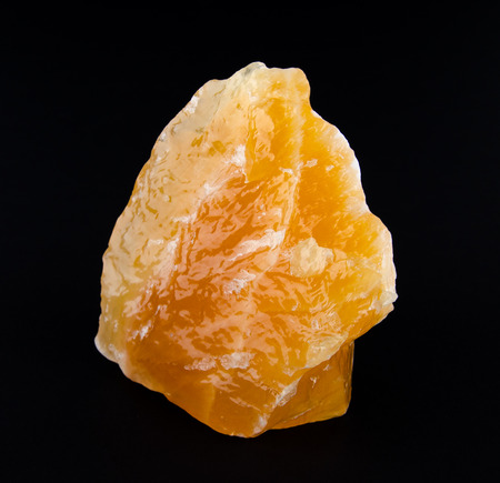calcite: Yellow and orange calcite, found in Mexico on black background - a carbonate mineral and polymorph of calcium carbonate, CaCO3  Stock Photo