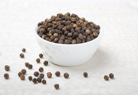 piperaceae: Black Pepper - Dried black peppercorns in a white porcelain bowl on white textile made of linen