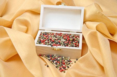 piperaceae: Pepper Treasure - Mixed dried peppercorns in a wooden box on cream colored silk