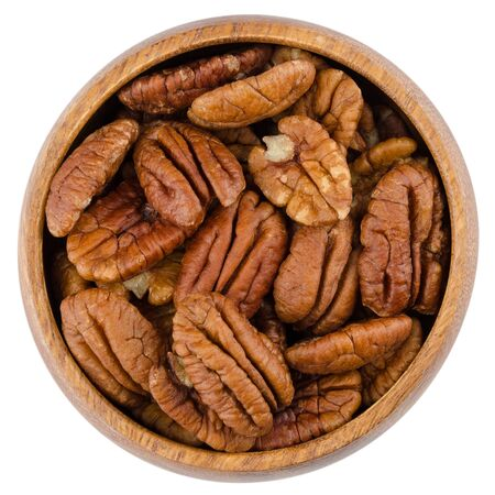 hickory nuts: Pecan halves in a wooden bowl from above, isolated on white background.