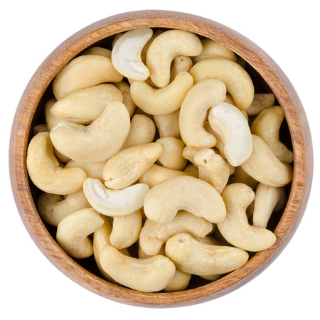 Bowl With Cashew Nuts. Raw cashew nuts in a wooden bowl from above, isolated on white background. 版權商用圖片