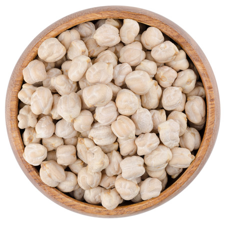 garbanzo bean: White chickpeas in a wooden bowl from above, isolated on white background. Stock Photo