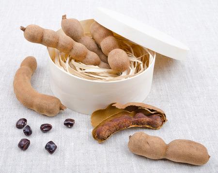 tamarindo: Frutas secas con semillas de tamarindo en una caja de madera en el lino. Una vaina abierta con pulpa dentro de su caparazón. Tamarindus indica.