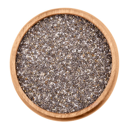 hispanica: Chia seeds in a bowl on white background. Raw edible fruits of Salvia hispanica of the mint family, Lamiaceae, in a wooden bowl. Isolated, macro photo and close up from above.