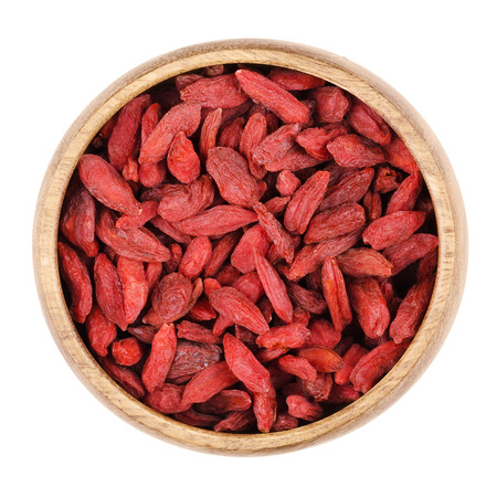 lycium: Goji berries in a bowl on white background, also called wolfberry. Dried red fruits and seeds of Lycium barbarum and Lycium chinense. Edible, raw and organic food. Isolated close up macro photo.