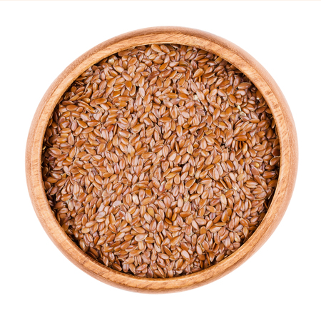Brown flaxseeds in a wooden bowl on white background. Also known as common flax or linseed. Raw edible food. Linum usitatissimum of the Linaceae family. Isolated, macro photo and close up from above. 版權商用圖片