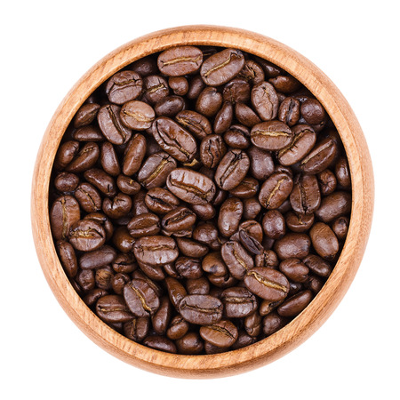 pits: Arabica coffee beans in a wooden bowl on white background. Unpulverized roasted brown pits of the coffee cherries. Isolated close up macro photo from above.