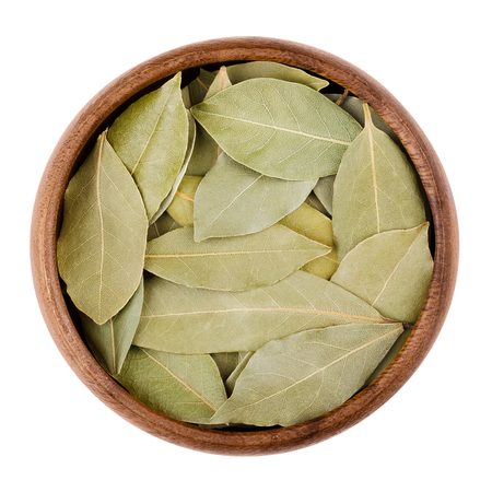 edible leaves: Dried bay leaves in a bowl on white.  Aromatic leaves of Laurus nobilis, also called laurel, used for seasoning in cooking. Edible, raw and organic food. Isolated close up macro photo.