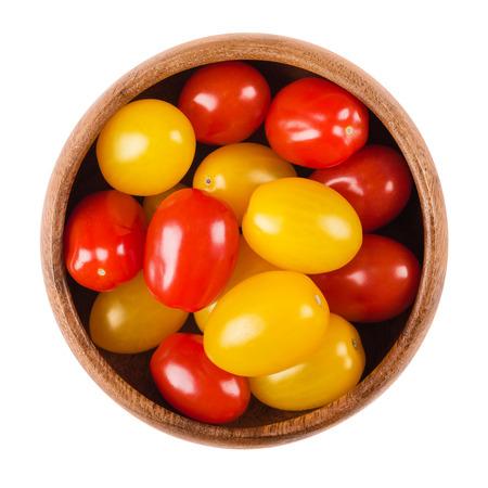 kulinarne: pomidory koktajlowe w drewnianej misce na białym tle. Żółte i czerwone dojrzałe owoce Solanum lycopersicum, rodzaj owoców jagodowych, ale są uważane kulinarnych warzyw. Jadalne, surowe, żywność ekologiczna. makro