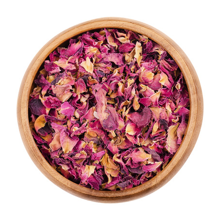 teas: Dried rose petals in a wooden bowl on white background. Used for perfumes, cosmetics, teas and baths. Purple colored organic herb. Isolated macro photo close up from above.