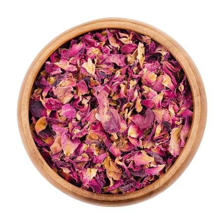 rosas blancas: Pétalos de rosas secas en un recipiente de madera sobre fondo blanco. Se utiliza para perfumes, cosméticos, infusiones y baños. Púrpura orgánica de hierbas de color. Aislado de macro fotografía de cerca desde arriba.