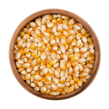 Unpopped popcorn in een houten kom op een witte achtergrond. Een type graan dat expandeert uit de kernel en opgeblazen bij verwarming. Yellow zaden, eetbaar, rauw en veganistisch eten. Geïsoleerde macro foto close-up. Stockfoto