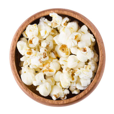 popped: Popped popcorn in a wooden bowl on white background. Butterfly shaped popcorn puffed up from the kernels, after it has been heated. Edible, raw and vegan food. Isolated macro photo close up from above Stock Photo