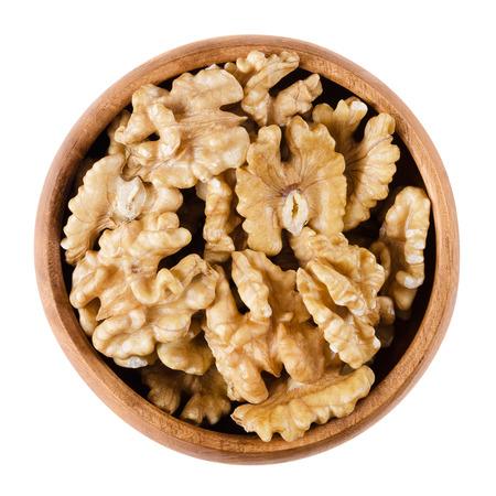 흰색 배경에 나무 그릇에 호두 커널 halfs입니다. 브라운은 일반적인 호두, 호두 나무의 씨앗을 건조시켰다. , 식용 유기 및 채식 음식. 격리 된 매크로  스톡 콘텐츠