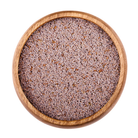 psyllium: Psyllium seed husks in a wooden bowl on white background. Dried fruits, used in cooking  to produce an edible mucilage, a thick gluey substance. Also used as a dietary fiber. Isolated macro close up.