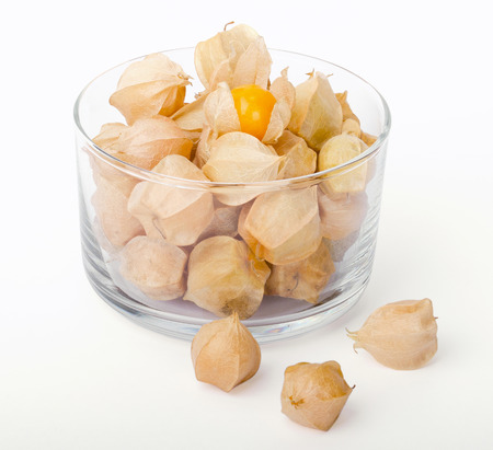 edible plant: Physalis in a glass bowl on white background. Edible ripe fruits of Physalis peruviana, a plant in the nightshade family. Light brown papery husks fully encloses the orange fruits. Macro food photo.
