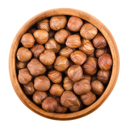 corylus: Hazelnuts in a wooden bowl on white background. Shelled ripe seeds of a cultivated Corylus species. Edible raw fruits. Isolated macro food photo close up from above.