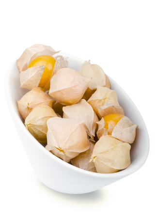 edible plant: Physalis berries in white porcelain bowl over white. Edible ripe fruits of Physalis peruviana, a plant in the nightshade family. Light brown papery husks fully encloses the orange fruits. Macro photo.