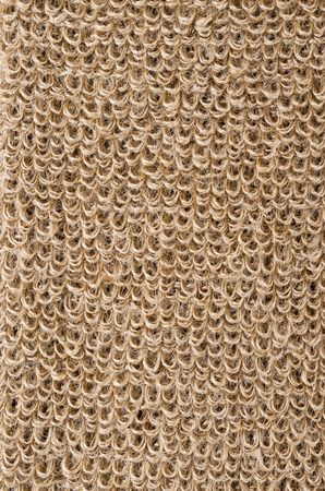 rough: Rough flax fabric with loops. Natural flax fibres are processed to a coarse fabric, used for massage straps and gloves. Solid yarn with brown ochre color. Isolated macro photo close up.