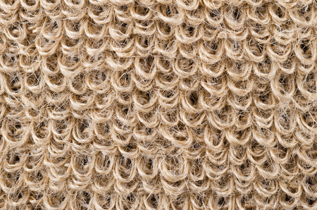 fibres: Loops of rough flax fabric. Natural flax fibres are processed to a coarse fabric, used for massage straps and gloves. Solid yarn with brown ochre color. Isolated macro photo close up. Stock Photo