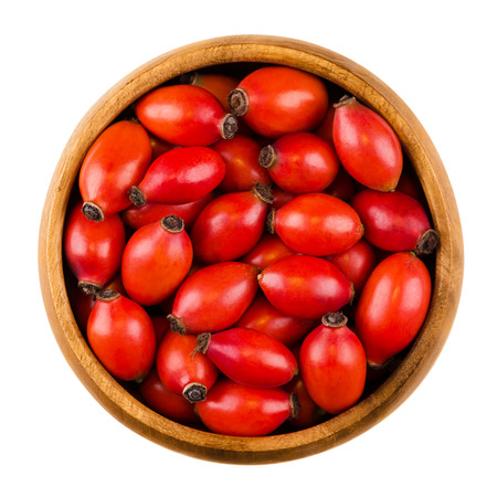 teas: Rose hips in wooden bowl over white, also rose haw or rose hep. Ripe red fruits of roses. Used for herbal teas, jam and can be eaten raw. One of the richest vitamin C sources available in plants.