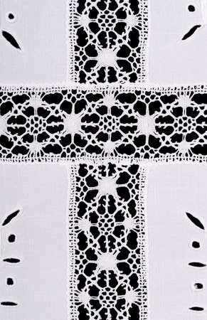 broderie: motiv croix latine whitework nappe en lin de broderie. la décoration de l'artisanat Reticella avec fil. coutures blanches sur toile de lin blanc. Macro photo close up de haut sur fond noir. Banque d'images