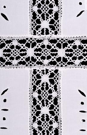bordados: motiv de cruz latina en whitework mantel de lino bordado. decoración de la artesanía Reticella con hilo. costuras blancas en el lino blanco. foto de primer plano macro desde arriba sobre fondo negro.