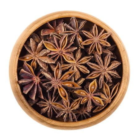 ajenjo: semillas de anís estrella en un cuenco de madera sobre blanco. Las frutas secas de Illicium verum, también chino anís estrellado o badiam. Se parece mucho a anís en sabor. Se utiliza para la cocción, sambuca, el pastis y el ajenjo.