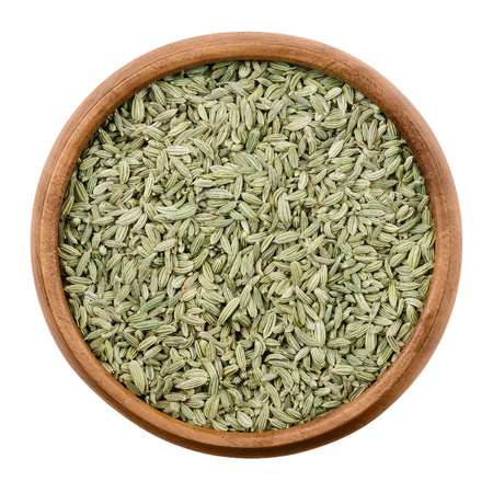 foeniculum vulgare: Fennel seeds in a wooden bowl on white background. Dried fruits of Foeniculum vulgare, an aromatic and flavorful herb with culinary and medicinal uses. Isolated macro photo close up from above. Stock Photo