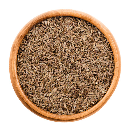 aroma bowl: Caraway seeds in wooden bowl on white background. Dried whole fruits of Persian cumin, Carum carvi, with anise like flavor and aroma used as spice in cuisine. Isolated macro photo close up from above.