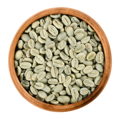 unroasted: Green Arabica coffee beans in a wooden bowl on white background. Unroasted pits of the coffee cherries. Isolated close up macro food photo from above.