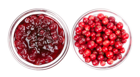 mountain cranberry: Lingonberry jam and lingonberries in glass bowls over white. Fresh red fruits of Vaccinium vitis-idaea, also mountain cranberries, partridgeberries or cowberries. Staple food in Scandinavian cuisine.
