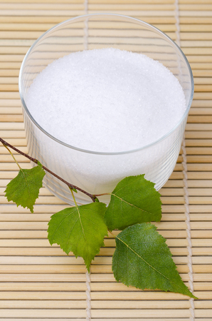 Xylitol birch sugar in a glass bowl with birch leaves on a bamboo mat. White granulated sugar alcohol, substitute used as sweetener that taste like table sugar, extracted from the wood of birch trees. Stock Photo